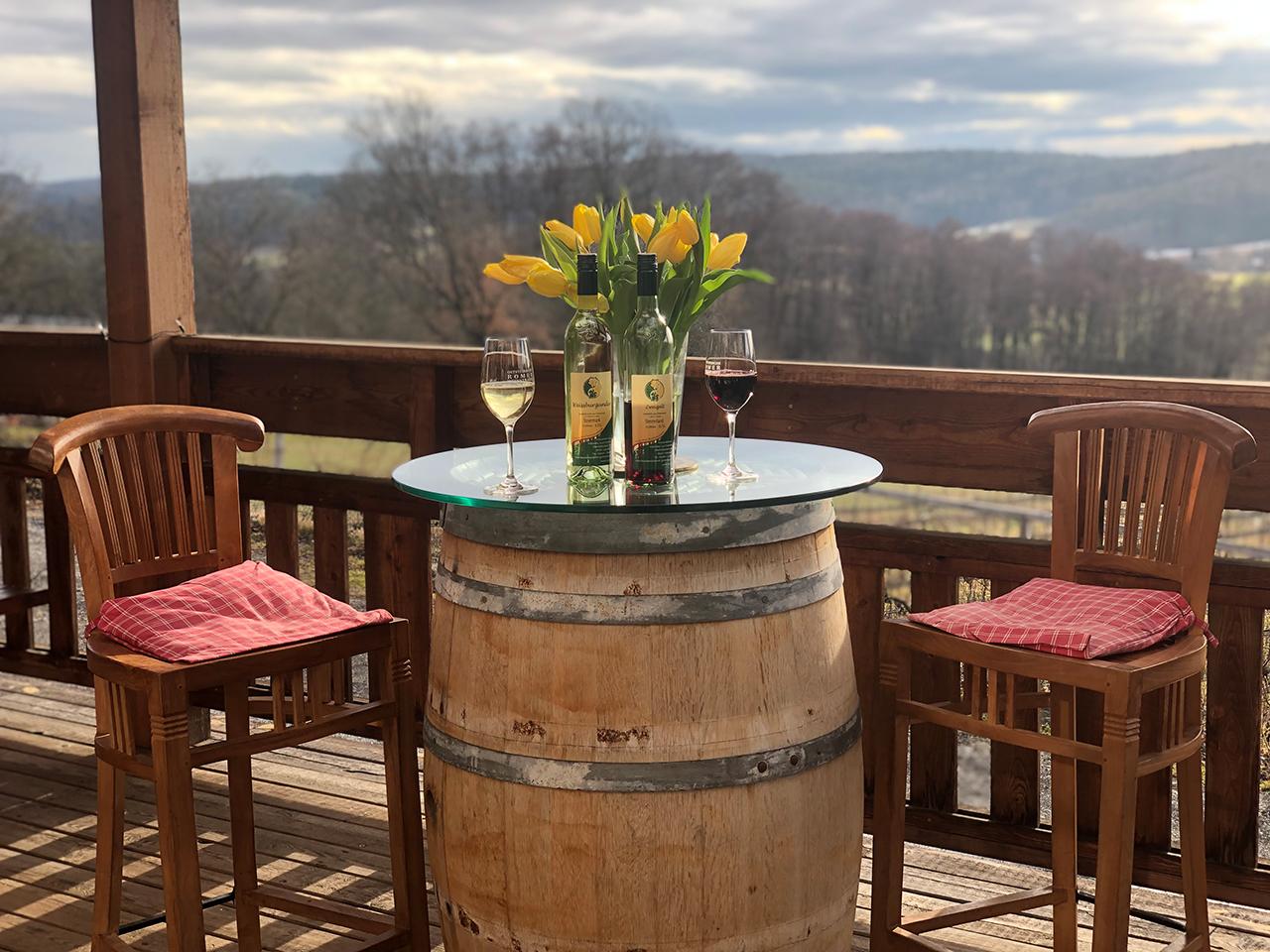 Stehtisch auf der Terrasse mit Blumendeko und Weinen